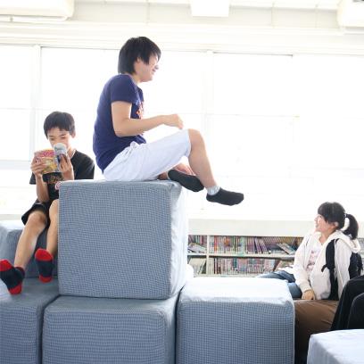 ひと教室のかべを取りはらい、じゅうたん敷きになっている空間。上ばきを脱いでくつろいだり、マンガを読んだり、友だちとゲームをしたり、『でこぼこ』と呼ばれる大きなブロックを積み上げて遊んだり、思い思いの過ごし方をしています。